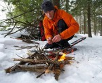When building survival fire in bad weather make sure to use a platform to get the fire off the snow or damp ground.  The platform should be substantial enough not to melt into the snow as the fire burns.  Photo Source: overhang.ca