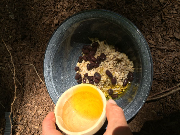 In a separate bowl, combine the black beans, brown rice, and two tablespoons of olive oil. Mix well.