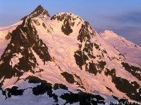 USA, Washington, North Cascades NP, Mt Shuksan at sunrise with Mt Baker in the distance from the summit of Ruth Mt